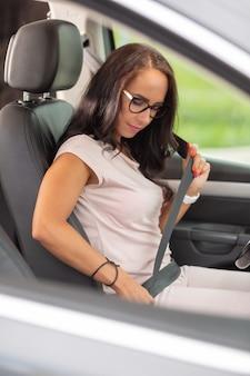 Una donna con gli occhiali allaccia la cintura di sicurezza per sicurezza dopo essere stata seduta in macchina.