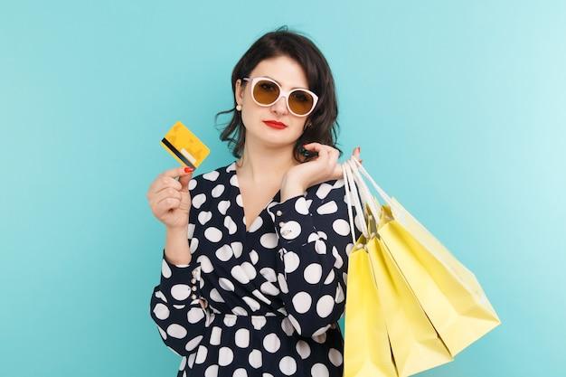 Donna con gli occhiali in possesso di carta e borse su sfondo blu.