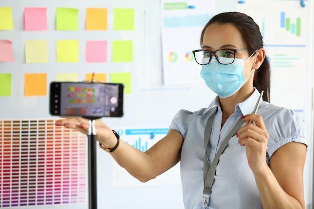 Donna in occhiali, camicia e maschera protettiva registra video sul suo telefono
