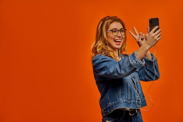 La donna con gli occhiali con le cuffie in una giacca di jeans mostra un simbolo di pace e scatta una foto al telefono