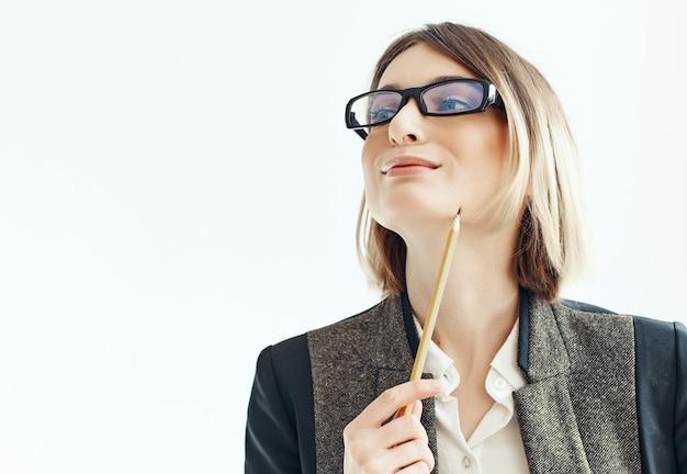 Donna in vetri con il blocco note in fondo chiaro dell'ufficio delle mani