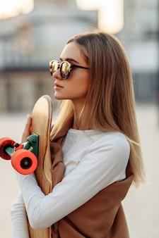 Donna con gli occhiali con un pattino in mano. longboard in giro per la città. foto di alta qualità
