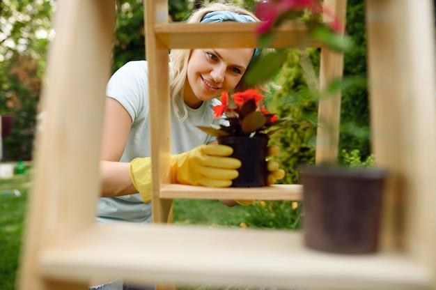 Donna in guanti che crescono fiori in vaso in giardino