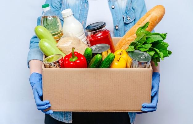 Donna in guanti che tengono le forniture alimentari della scatola di donazione per la gente in isolamento. prodotti essenziali: olio, conserve, cereali, latte, verdure, frutta