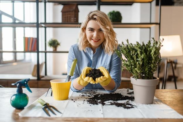 La donna in guanti tiene il mucchio di torba per le piante domestiche