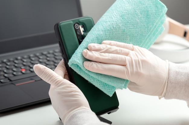 La donna in guanti pulisce il phomelaptop con tessuto umido e disinfettante durante il covid 19. disinfezione phome e tastiera del laptop con disinfettante alcolico da parte di una donna in maschera che si illumina sul posto di lavoro, scrivania.