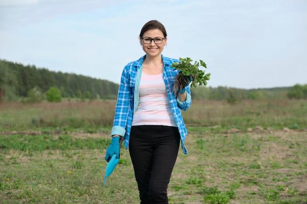 Donna in guanti con attrezzi da giardino che tengono il cespuglio di fragole
