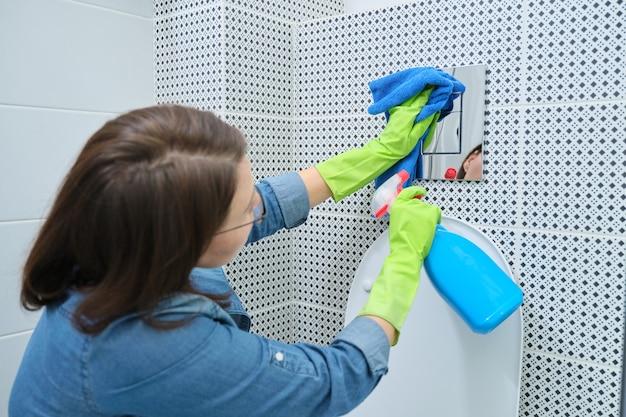 Donna in guanti con straccio che fa pulizia in bagno, pulizia e lucidatura pulsante wc cromato sulla parete piastrellata