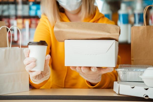 La donna in guanti lavora con ordini da asporto. cameriere che dà pasto da asporto durante il blocco del covid 19 della città, arresto del coronavirus. cottura da asporto, pizza caffè da asporto, food delivery.
