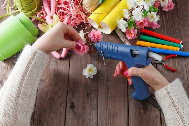 Donna colla fiori fatti a mano con pistola per fusione