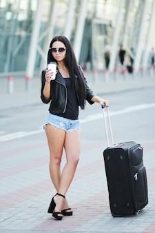 La donna va in viaggio con i bagagli nell'aeroporto internazionale di lviv e beve un caffè.
