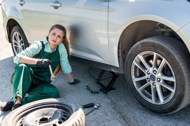 La donna sta per cambiare la ruota danneggiata sul ciglio della strada
