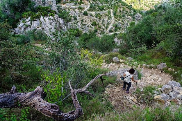 Donna che scende il sentiero di montagna tra pietre e vegetazione.