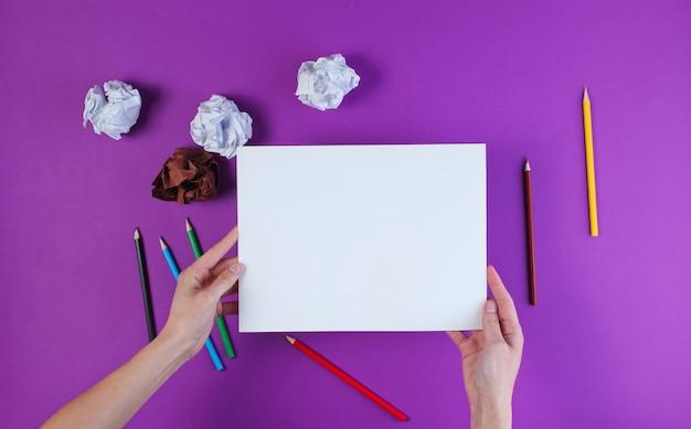 Donna che disegna con le matite colorate su una superficie viola con le palle di carta sgualcite.