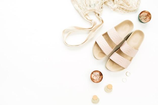 Composizione di moda in stile oro donna con pantofole, borsa di stringa, orecchini e anelli su superficie bianca