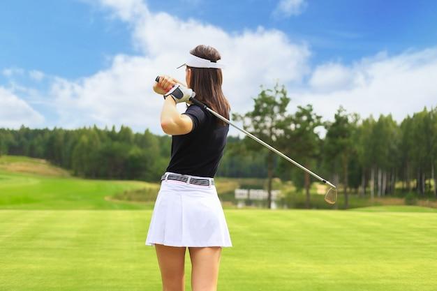 Golfista donna colpisce un fairway shot verso la club house.