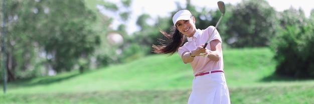 Giocatore di golf donna con mazza da golf in mano e palla volante dopo aver colpito