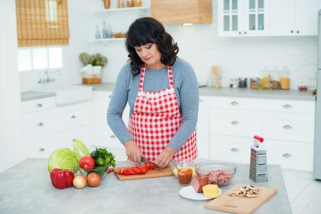 Una donna nonna con un grembiule a scacchi taglia fette di pomodori in cucina. ingredienti della pizza.