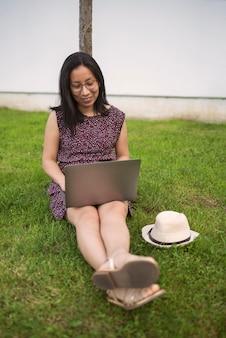Donna sull'erba che lavora con il laptop