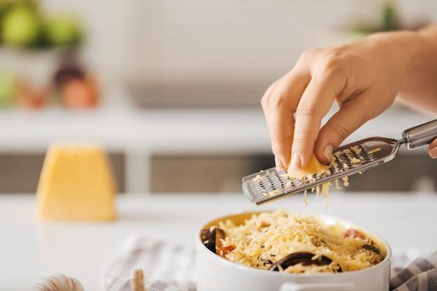 Donna grattugiare il formaggio in cucina, primo piano