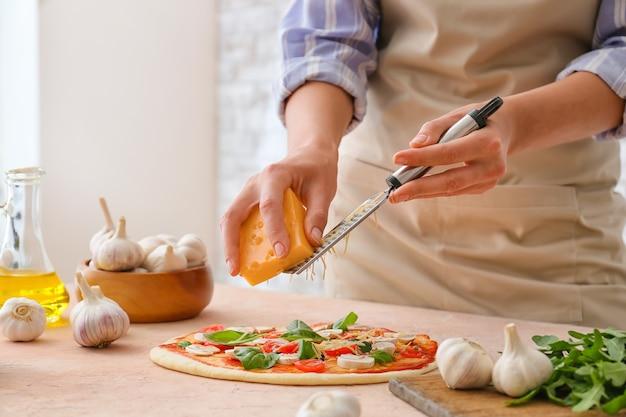 Donna grattugiare il formaggio sulla pizza in cucina
