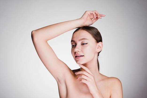 Una donna su uno sfondo grigio mostra le ascelle ben curate
