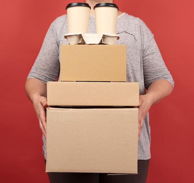 La donna in vestiti grigi tiene una pila di scatole di carta marrone e bicchieri usa e getta con caffè su uno spazio rosso, concetto di consegna di ordini online