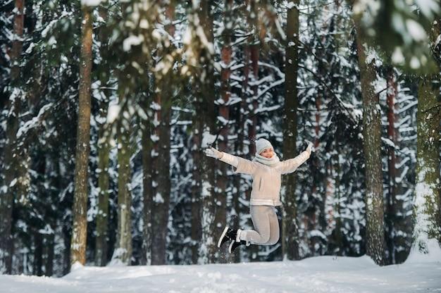 Una donna in abiti grigi salta emotivamente in una foresta invernale. ragazza nella foresta innevata del nuovo anno.