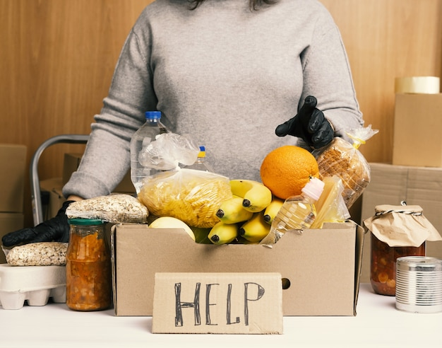 Donna in maglione grigio e guanti neri che tengono una scatola di cartone con generi alimentari, concetto di assistenza e volontariato, consegna del cibo