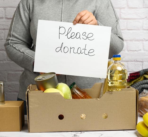 Una donna con un maglione grigio e guanti tiene in mano un foglio di carta con la scritta please donat, sul tavolo c'è una scatola di cartone con cibo e frutta. concetto di volontariato