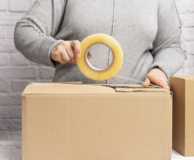 La donna in un maglione grigio tiene un rotolo di nastro adesivo e confeziona scatole di cartone marroni. concetto in movimento