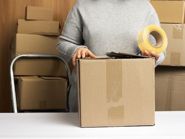 La donna in un maglione grigio tiene un rotolo di nastro adesivo e imballa scatole di cartone marroni su un tavolo bianco, dietro una pila di scatole. concetto in movimento