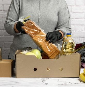 La donna in un maglione grigio sta imballando il cibo in una scatola di cartone, il concetto di assistenza e volontariato, donazione