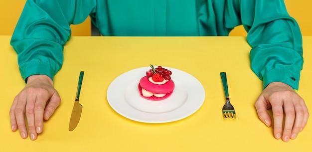 Donna in camicetta verde seduta accanto a una deliziosa torta