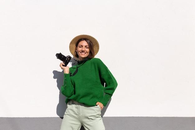 Donna in maglione casual verde e cappello all'aperto sul turista positivo felice muro bianco con telecamera professionale