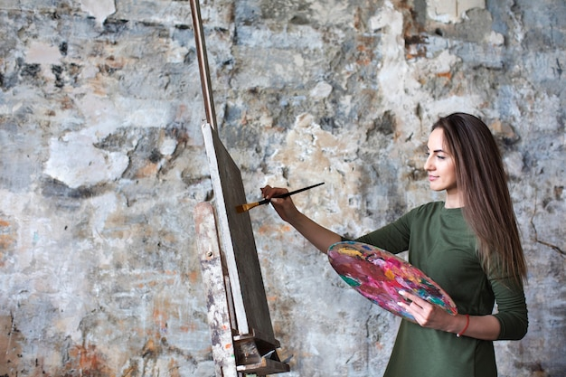 Donna in un abito verde in uno studio d'arte mentre si disegna su una tela.