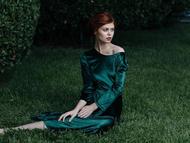 La donna in vestito verde si siede sul fascino dell'aria fresca della natura dell'erba.