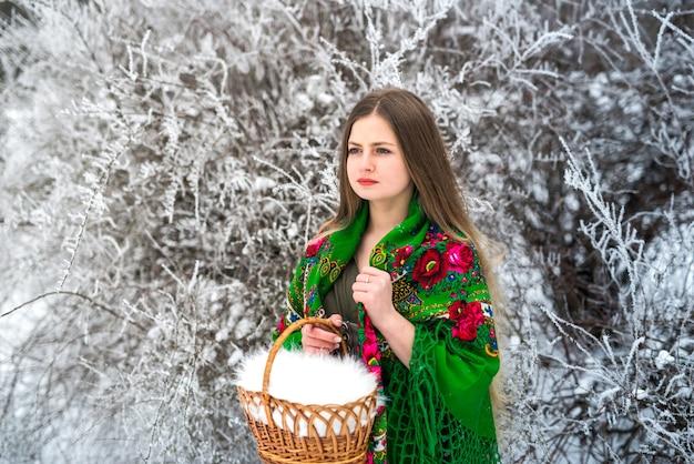 Donna in scialle verde che tiene cesto nel parco invernale