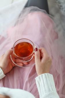 Donna in un maglione grigio e calzini caldi in possesso di una tazza di tè, mentre seduto su una coperta a maglia bianca