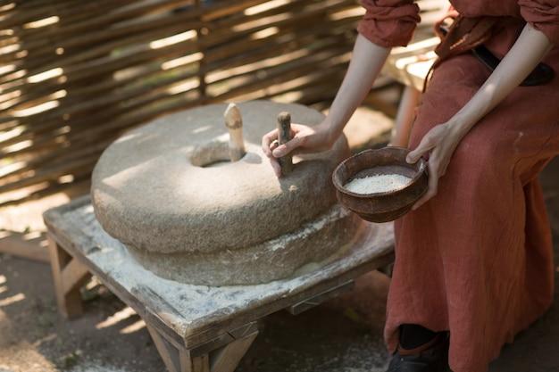 La donna macina il grano e produce farina sulla mola