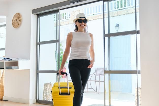 Turista dell'ospite della donna con la valigia nell'interiore della hall dell'hotel