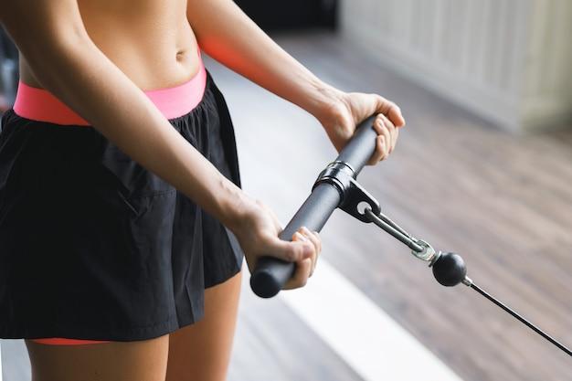 Donna in palestra esercizio di arricciatura del bicipite.