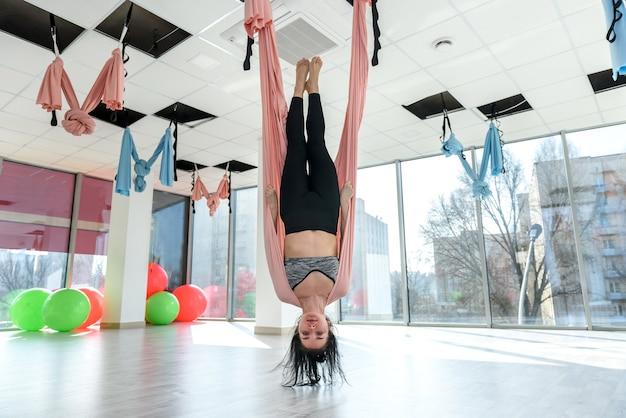 Donna in palestra facendo esercizi di yoga di volo