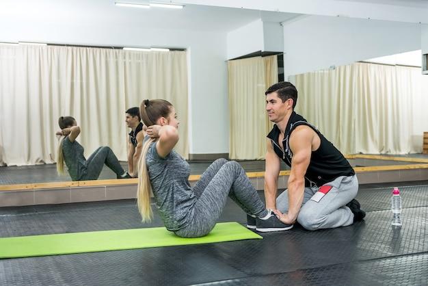 Donna in palestra facendo esercizi con istruttore Foto Premium
