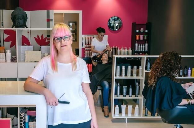 Parrucchiere della donna che sta in un salone di bellezza e dei capelli con i clienti
