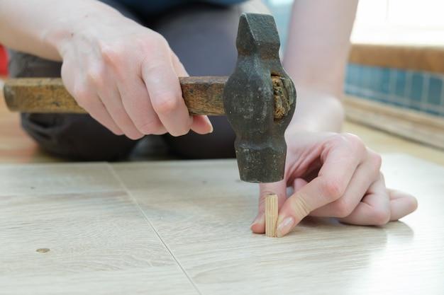 La donna martella un primo piano rotondo di legno del tassello a più scanalature delle mani di una donna