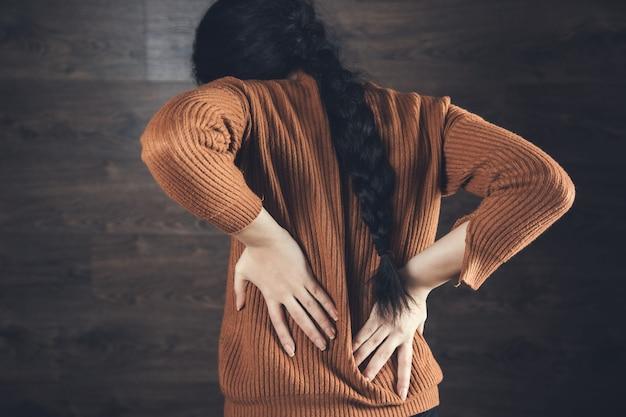 Mano di donna mal di schiena su sfondo scuro