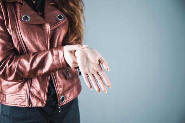 Mano della donna nella mano dolorante su gray