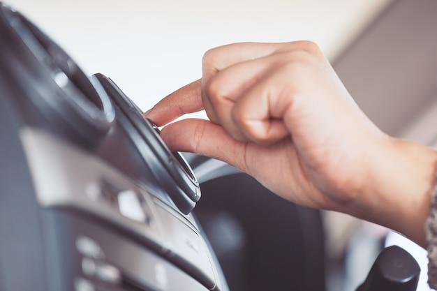 Mano della donna che regola il pannello di griglia del sistema di condizionamento d'aria dell'automobile nel tono d'annata di colore