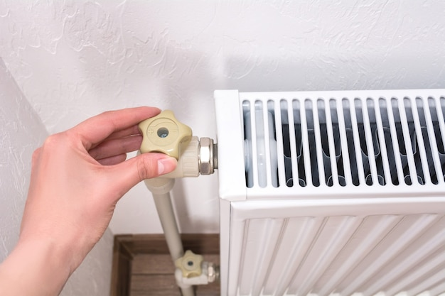 Mano della donna che regola la manopola del radiatore del riscaldamento. costoso concetto di costi di riscaldamento